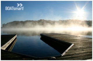 A picture of a dock with mist on the water.