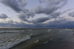 The sun was gone but the afterglow gave the shoreline an eerie feel,  punctuated by the dark clouds.