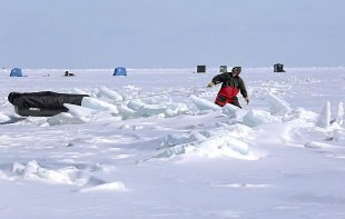 Tom Gavitt of Duluth pulls his ice-fishing sled through a pressure ridge of ice on Lake Superior on Tuesday, March 4, 2014, offshore from Duluth's Brighton Beach. Gavitt was one of many anglers who ventured onto the lake to fish for lake trout. (Steve Kuchera / Duluth News Tribune)