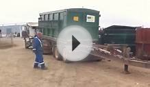 Waste Management roll off truck loading a pup trailer.